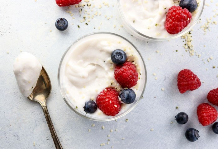 a spoonful of coconut milk yogurt, next to a cup of coconut milk yogurt topped with berries