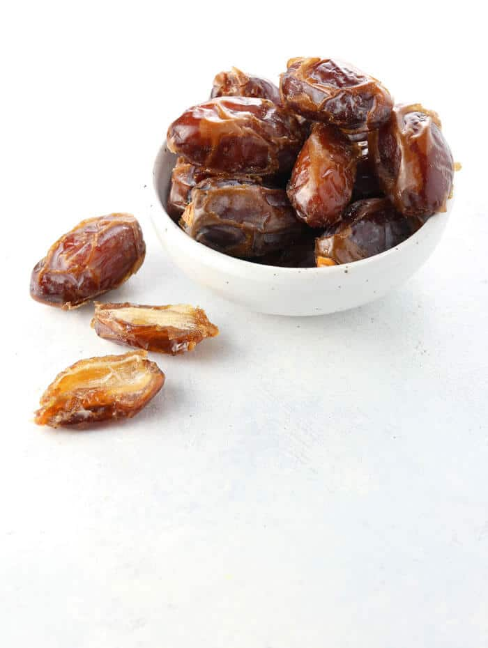 Medjool dates in a bowl on white background