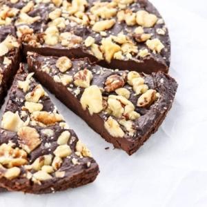 flourless vegan cake sliced with walnuts on top