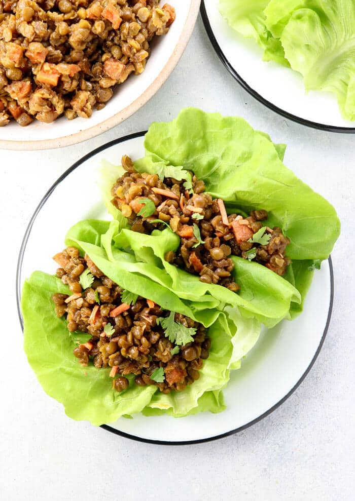 vegan thai lettuce cups on a white plate with butter lettuce leaves