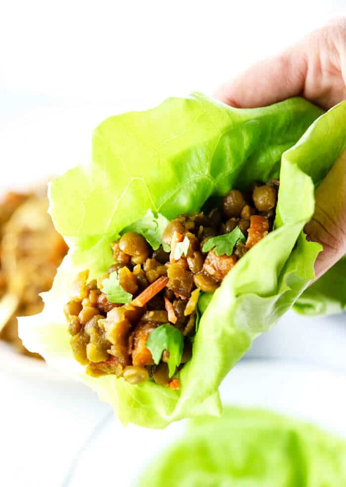 hand holding a Thai lettuce wrap full of split pea filling