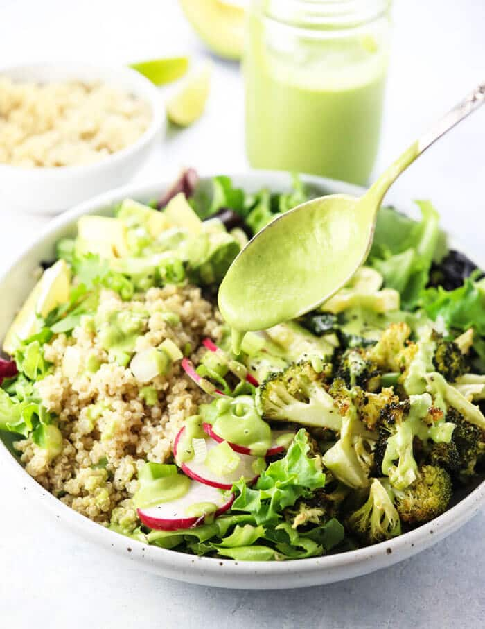 Healthy avocado cilantro dressing over a summer salad
