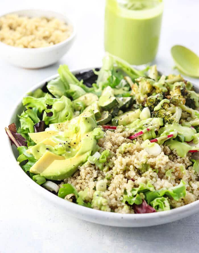 Summer salad topped with quinoa and avocado cilantro dressing
