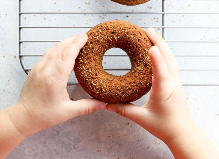 child's hands holding a baked donut