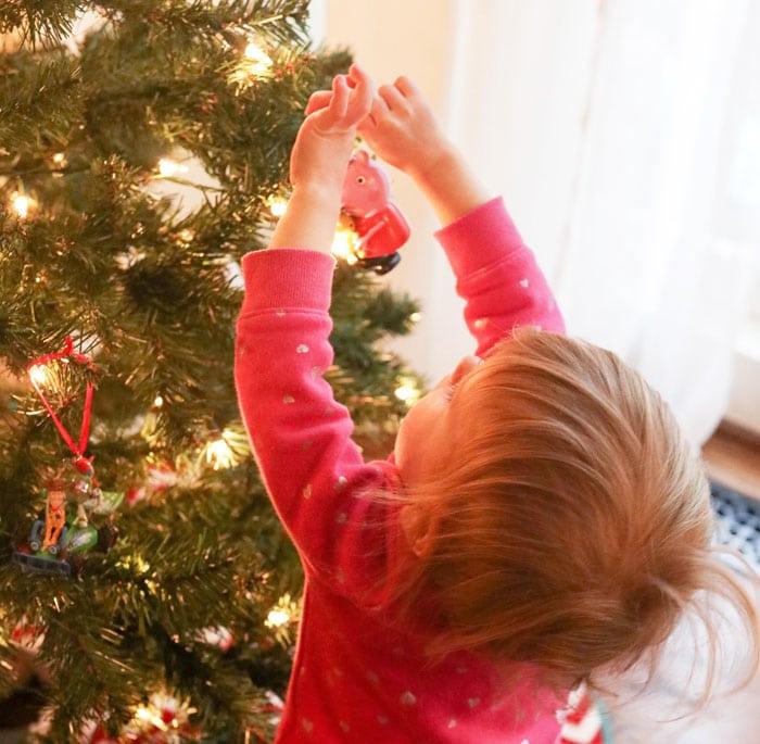 kid putting ornament on christmas tree