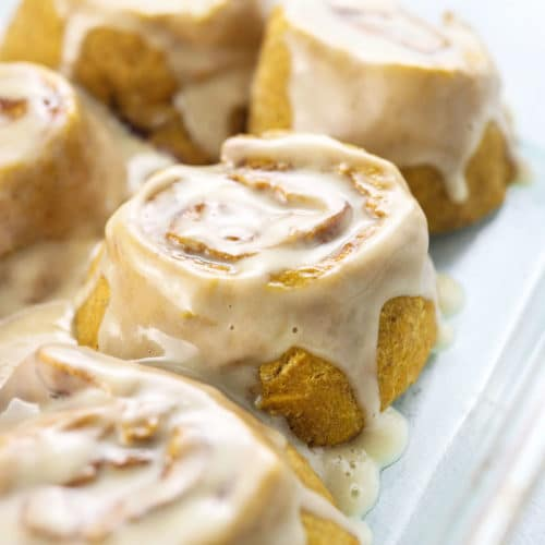 gluten-free vegan cinnamon rolls with icing in glass dish