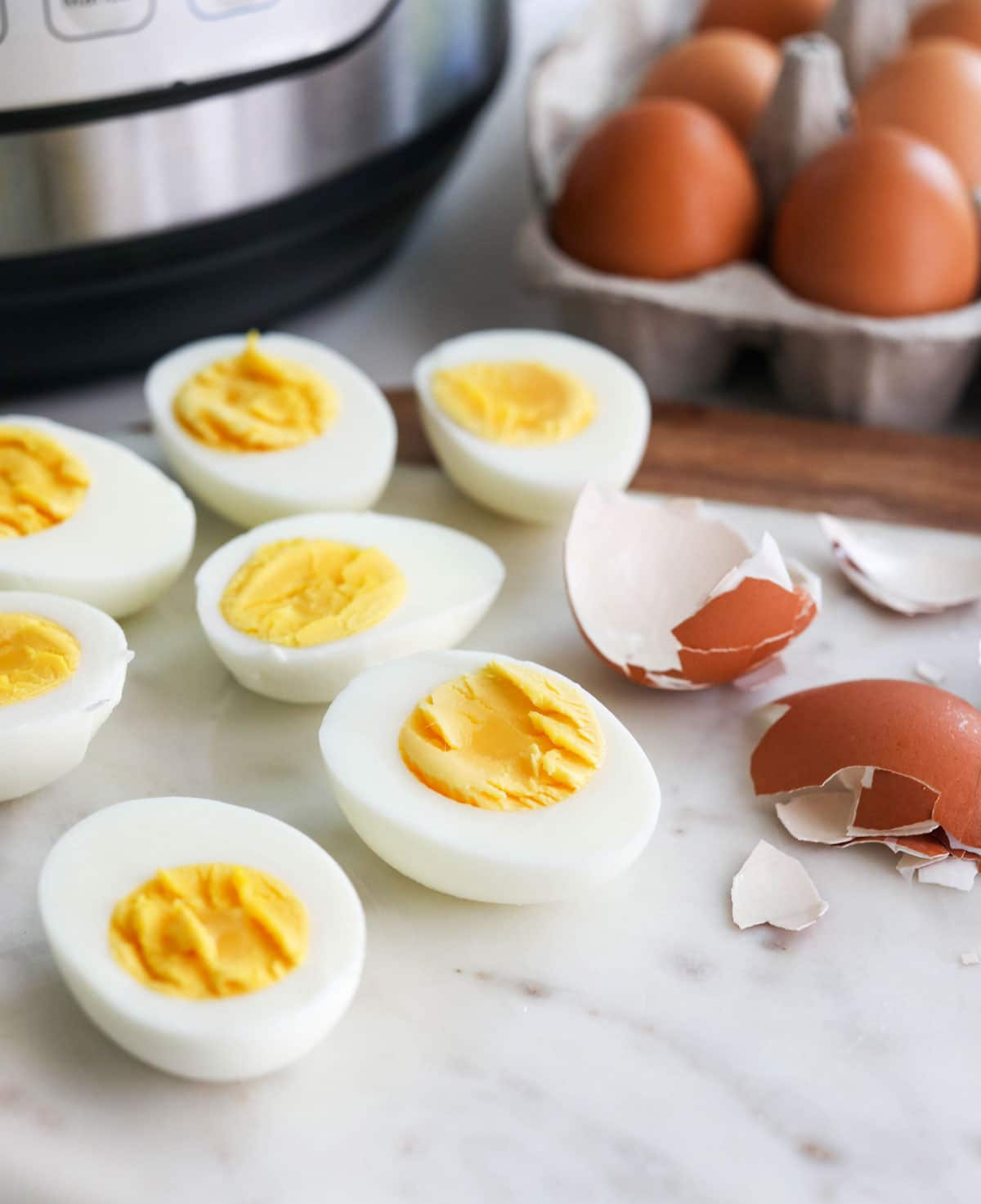 hard boiled eggs cut open with the peeled shell nearby