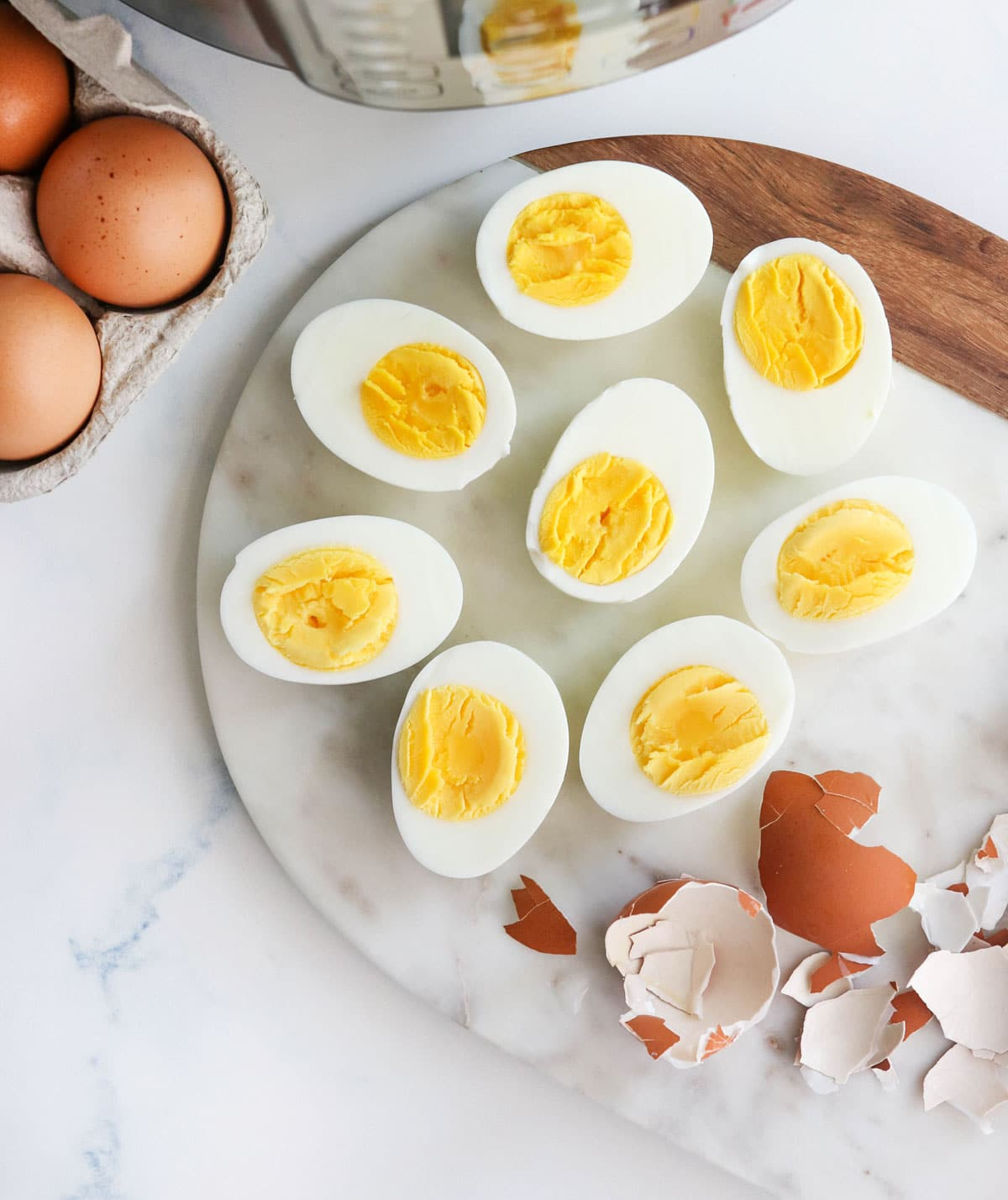 Instant Pot hard boiled eggs cut in half on a marble board