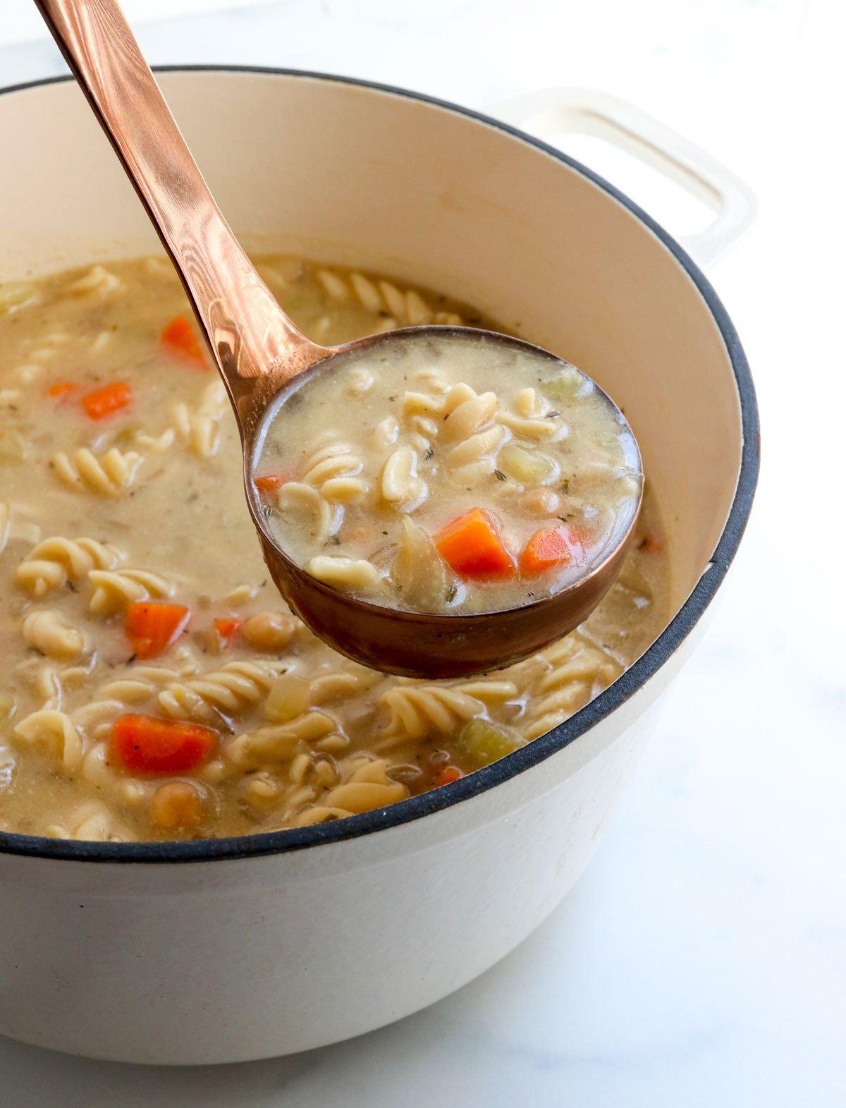 ladle lifting up chickpea noodle soup