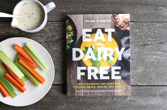 eat dairy free book on a wood table with carrots and celery and ranch