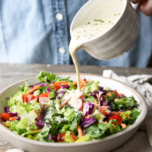 vegan ranch dressing pouring over salad