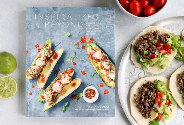 inspiralized and beyond book next to a plate of tacos