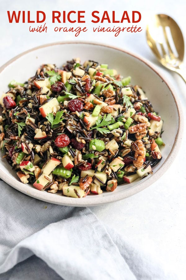 This cold wild rice salad is tossed in an orange vinaigrette, with crisp celery and apples, crunchy pecans, and sweet cranberries. It's a perfect salad for Thanksgiving, and can be made ahead of time for a fast and easy holiday meal loaded with Fall flavors. #healthyrecipe #salad #thanksgiving #holidayrecipe #dairyfree