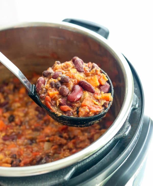 vegan chili in presure cooker on ladle