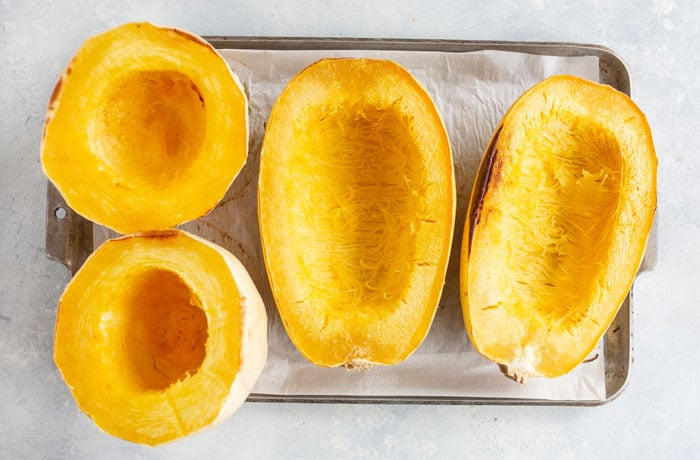 cooked squash on pan cut side up
