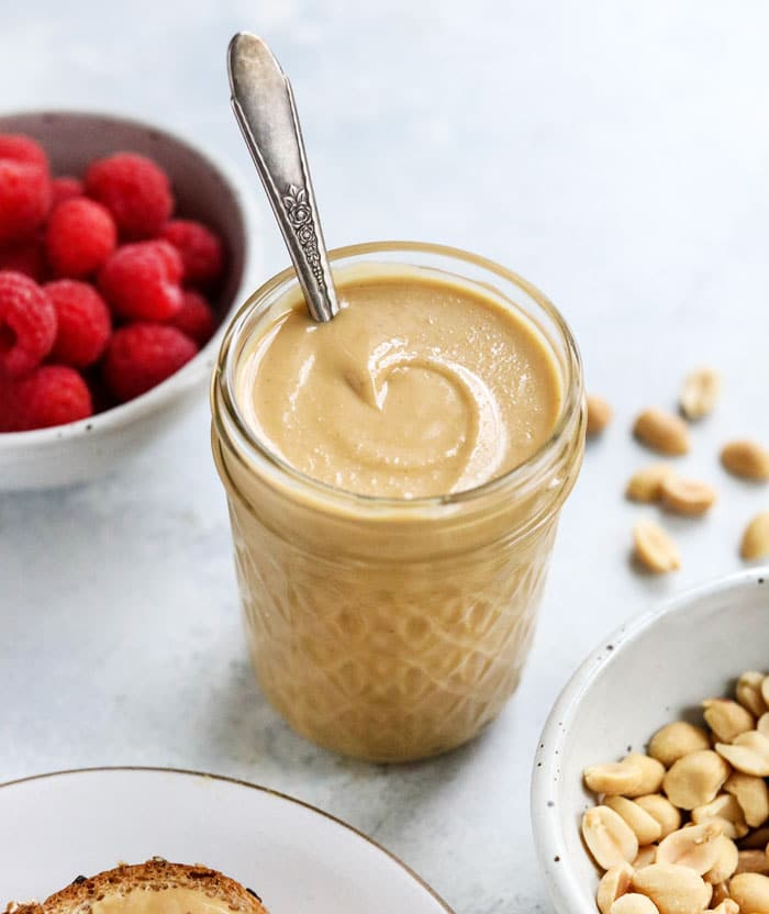peanut butter in jar with raspberries behind