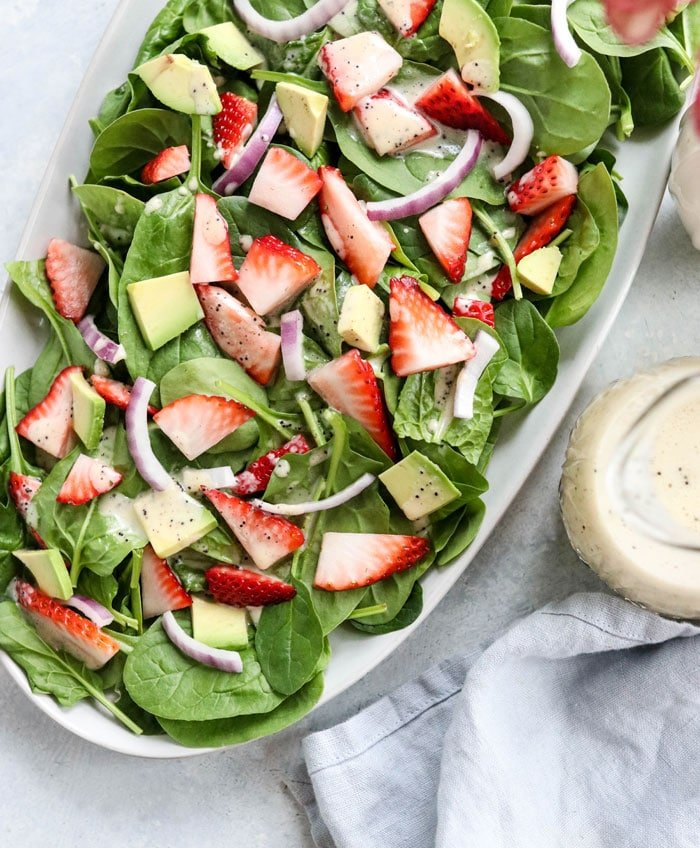 strawberry spinach salad overhead on a white plate
