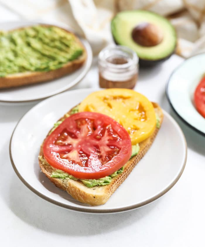 avocado toast with sliced tomatoes on top