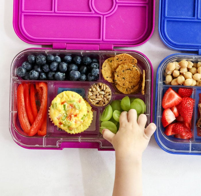 kid lunch box with hand reaching for grapes