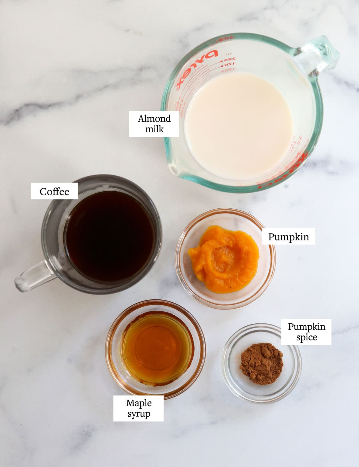 pumpkin, coffee, almond milk, maple syrup, and spice on a white surface