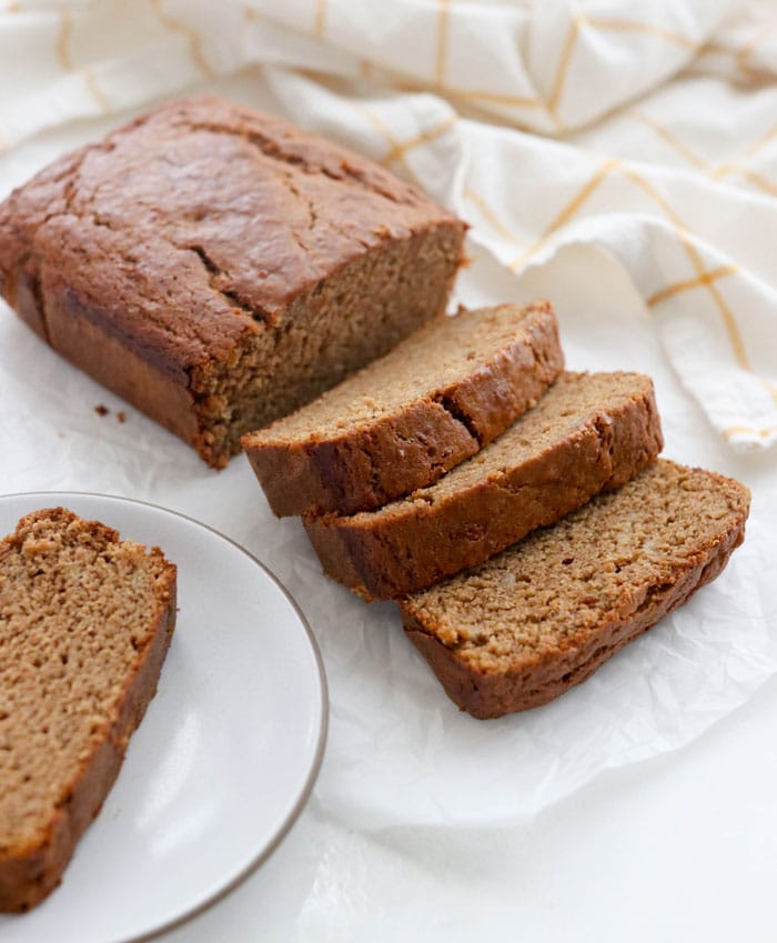 vegan banana bread sliced on a white surface