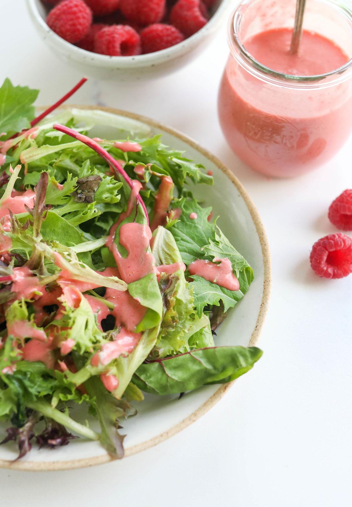 raspberry vinaigrette over leafy greens on plate