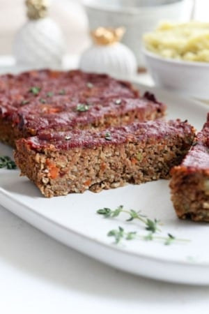vegan meatloaf sliced on a plate with thyme
