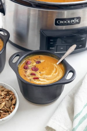 slow cooker pumpkin soup in black bowls