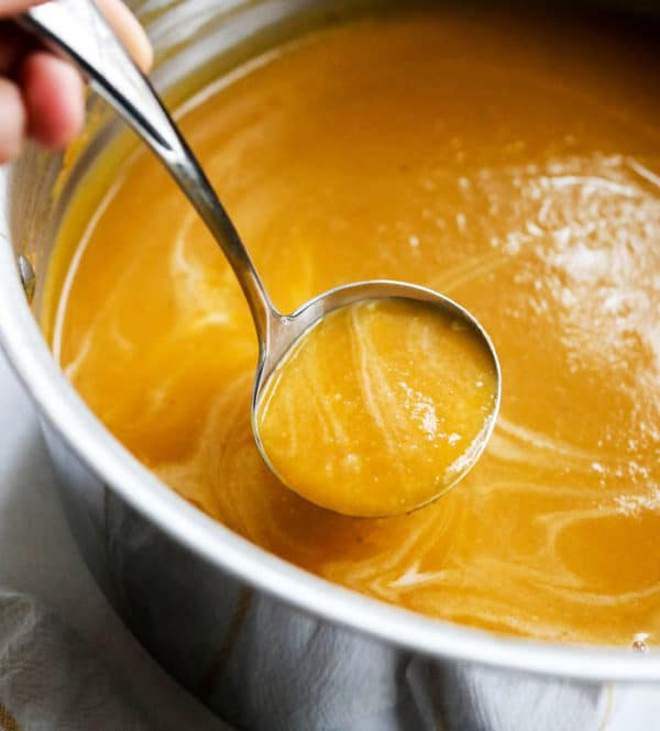 Butternut soup in a pot with a ladle