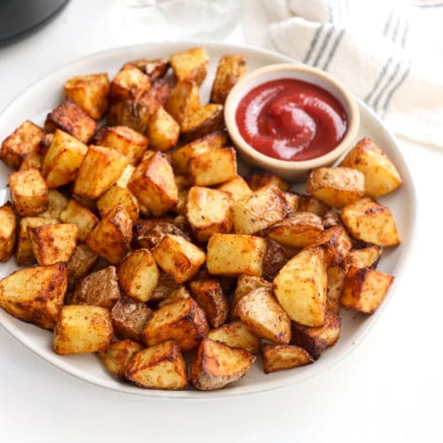 crispy air fryer potatoes on a plate with ketchup