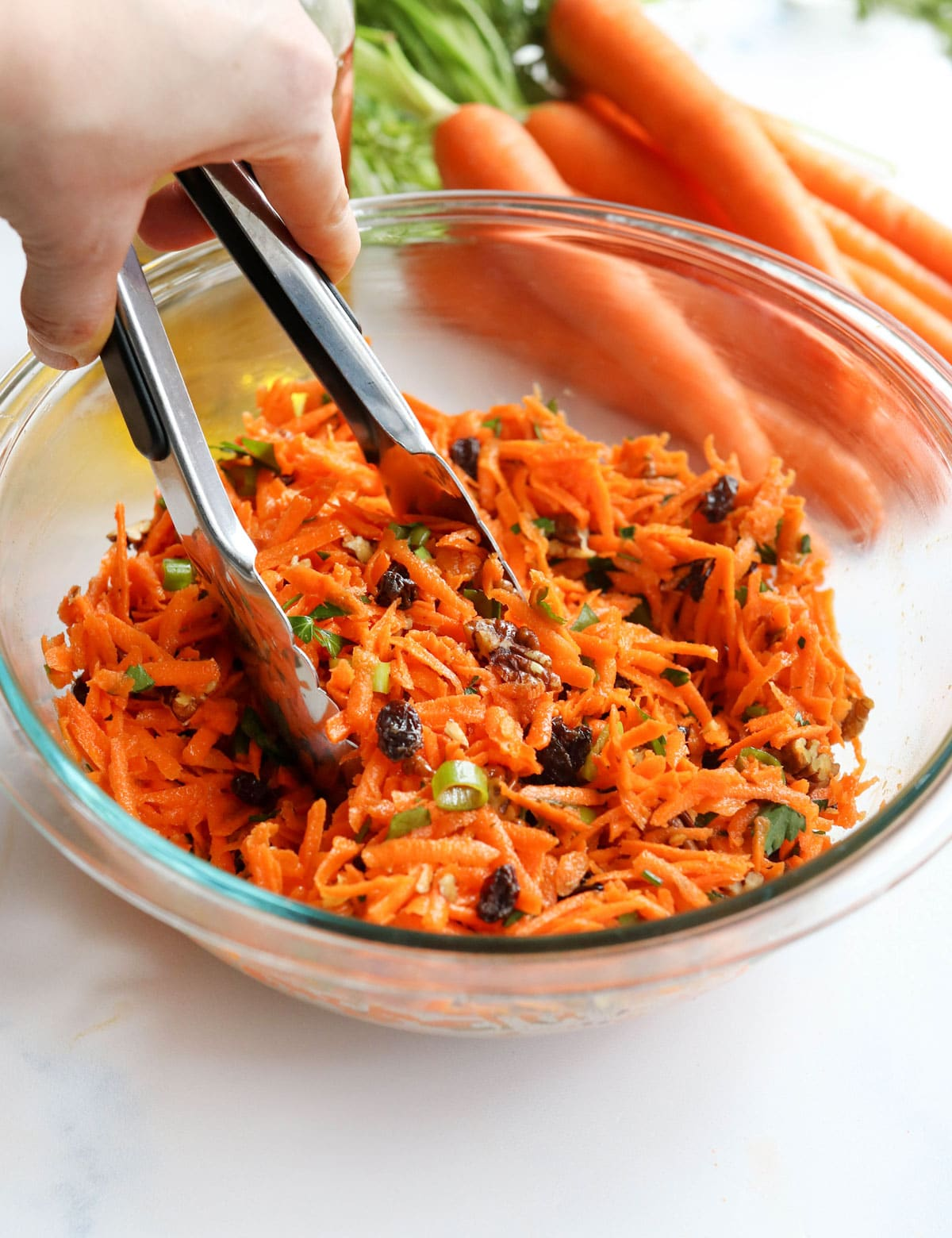 carrot salad in glass bowl with tongs