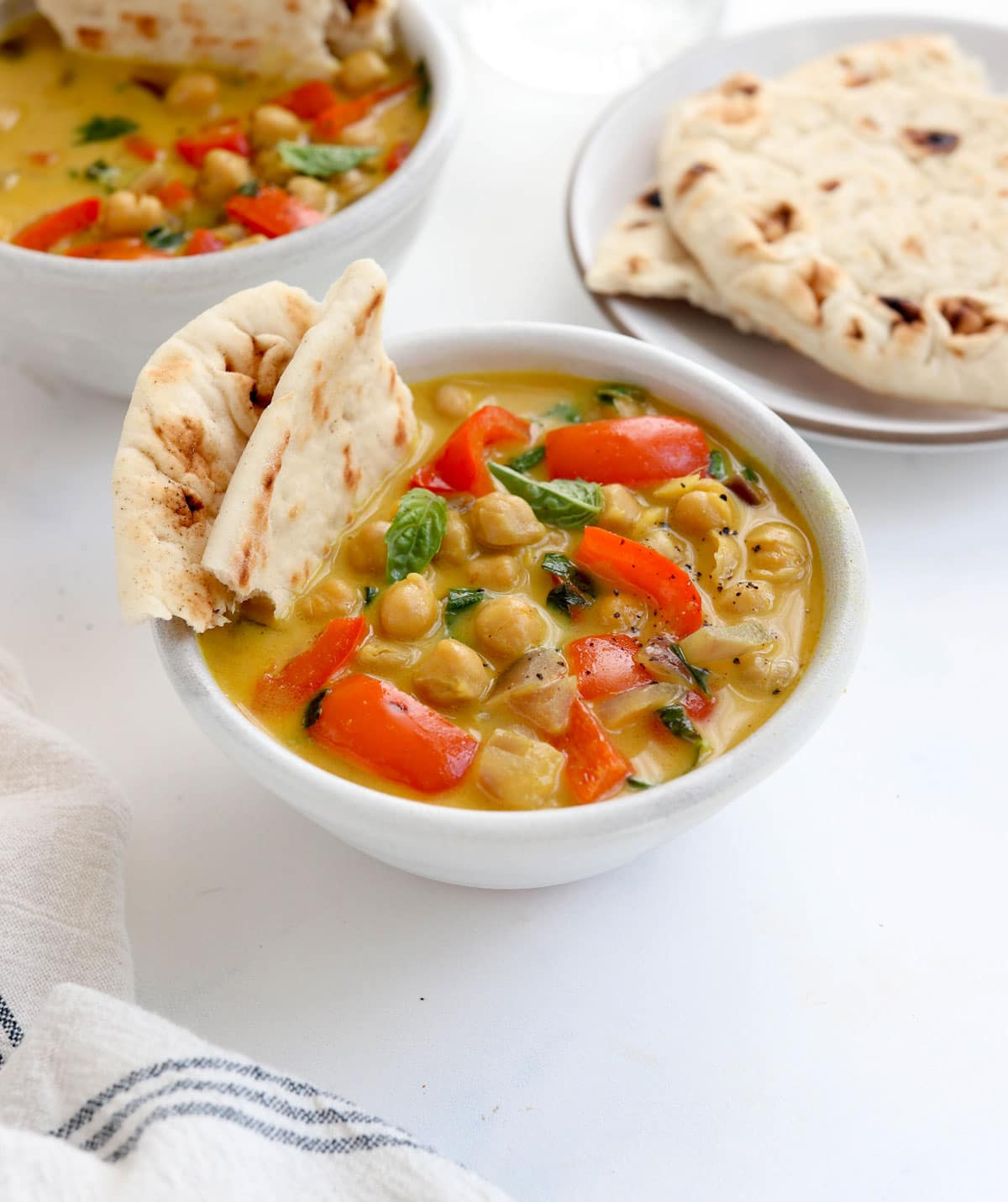 chickpea curry in white bowl with bell peppers