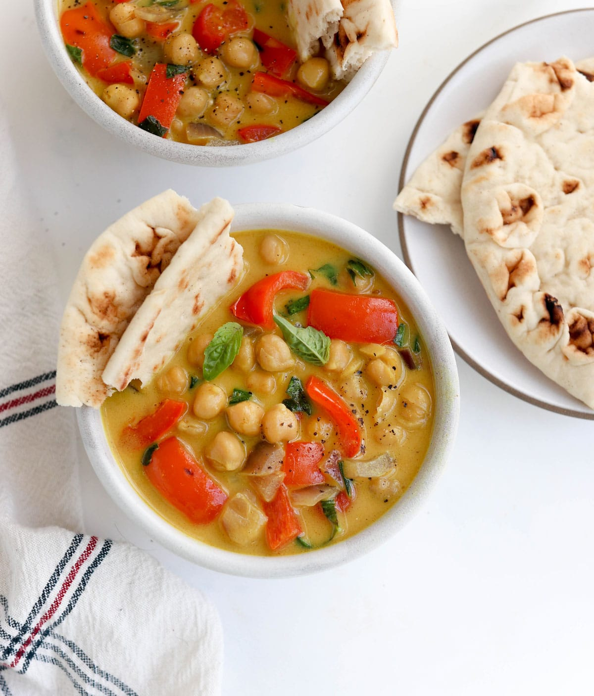 chickpea curry in bowl with naan bread