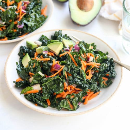kale salad on white plate with avocado