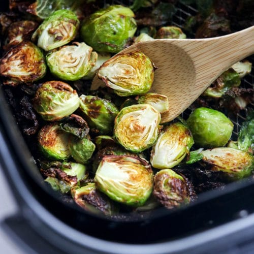 brussels sprouts in half in air fryer with spoon