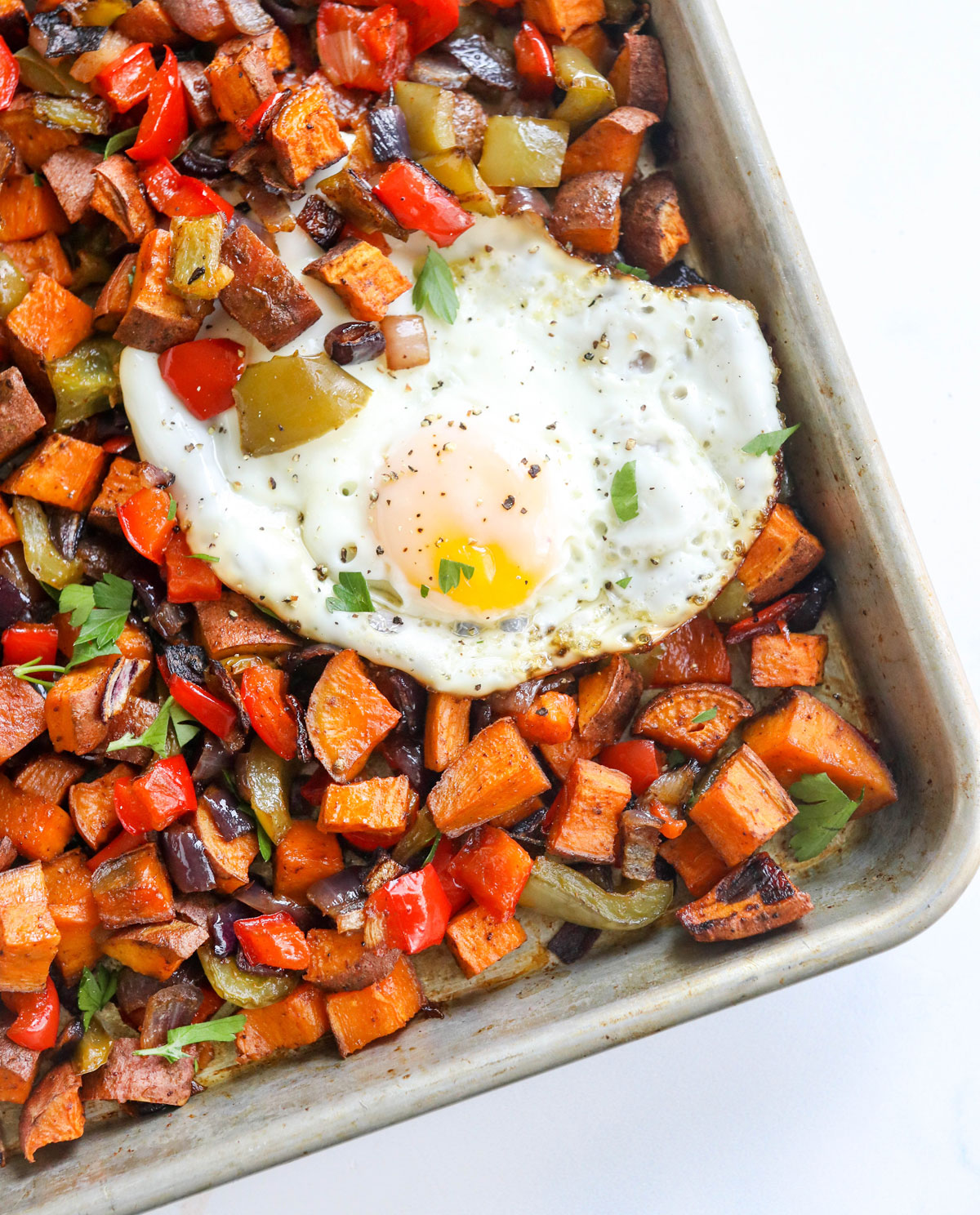 sweet potato hash on pan with eggs