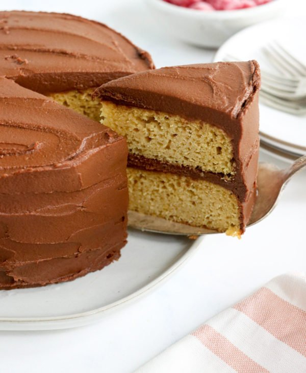 a slice of almond flour cake with chocolate frosting is being lifted out