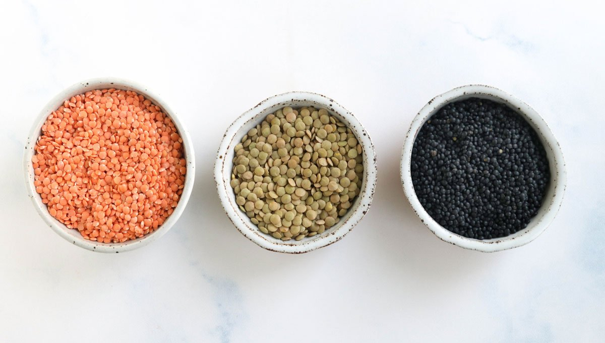 red green and black lentils in white bowls