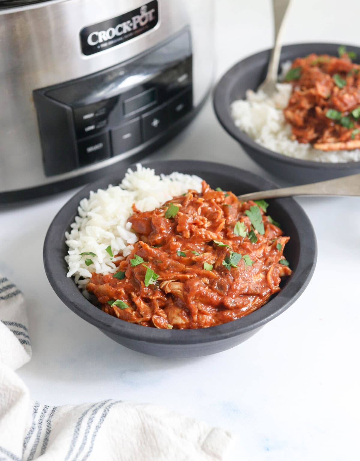 finished slow cooker butter chicken with white rice in a black bowl