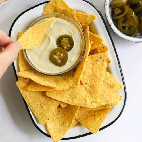 hand dipping chip into vegan nacho cheese