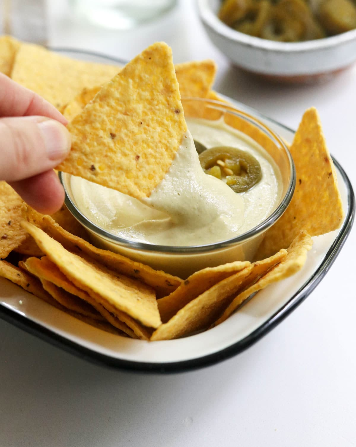 chip dipped in vegan nacho cheese sauce