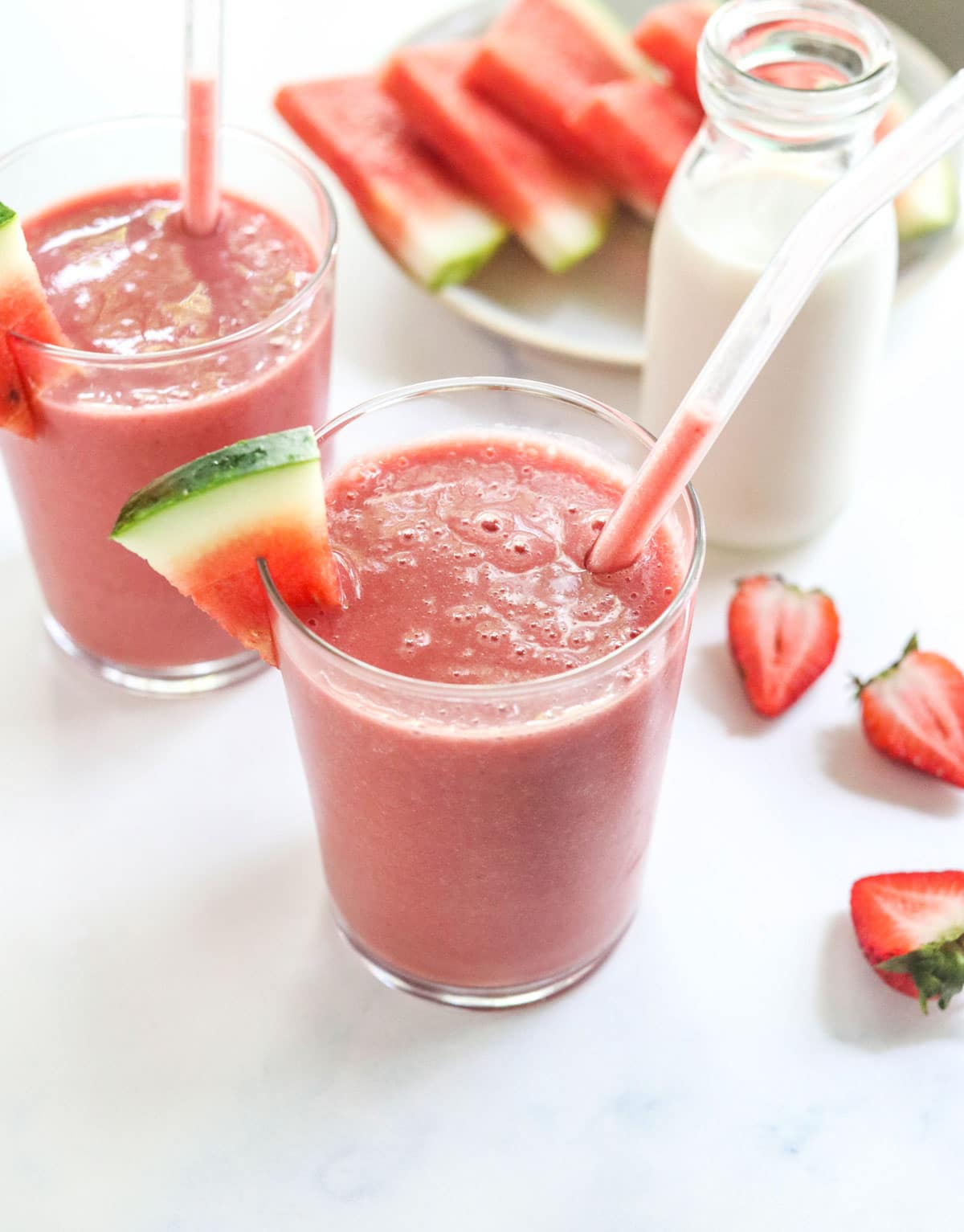 watermelon smoothie in two glasses with straws