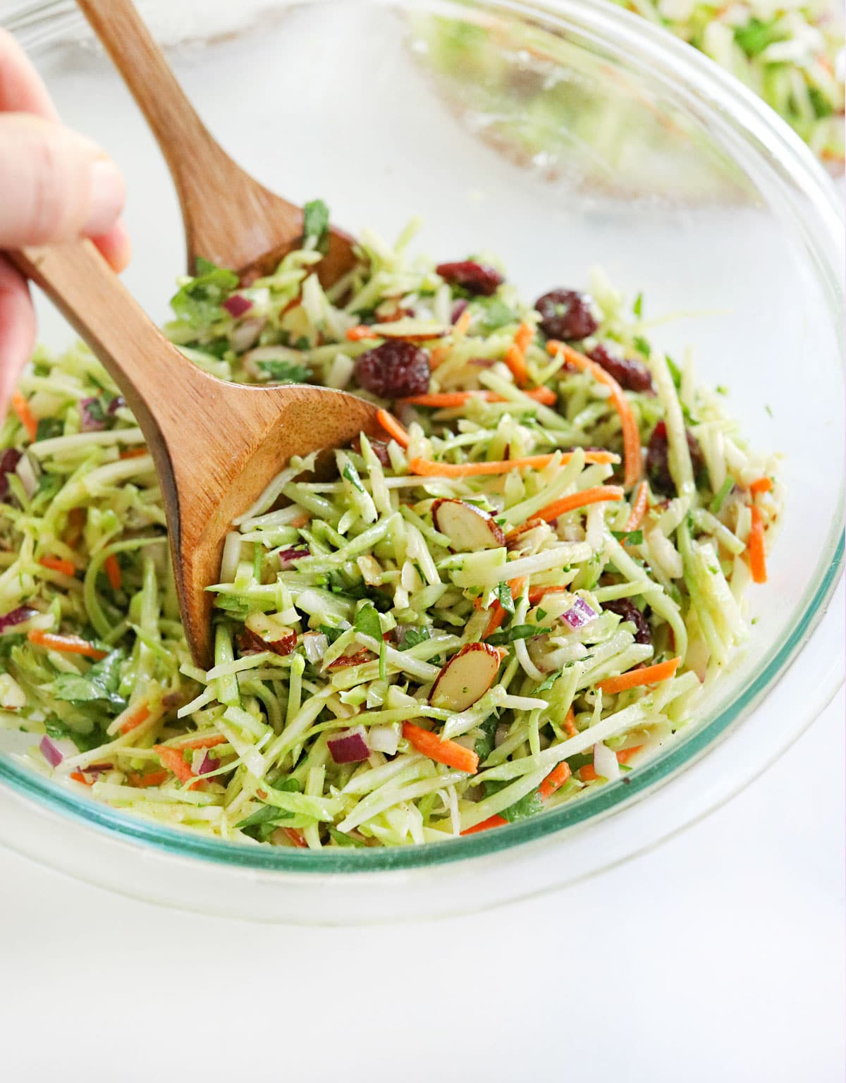 broccoli slaw tossed with wooden tongs