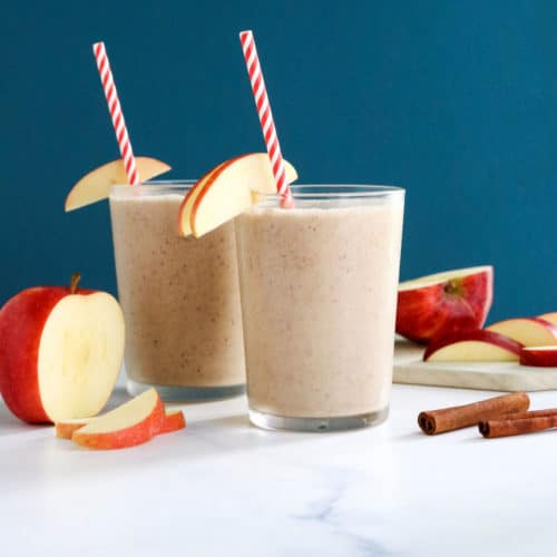 two glasses of apple smoothie with blue background