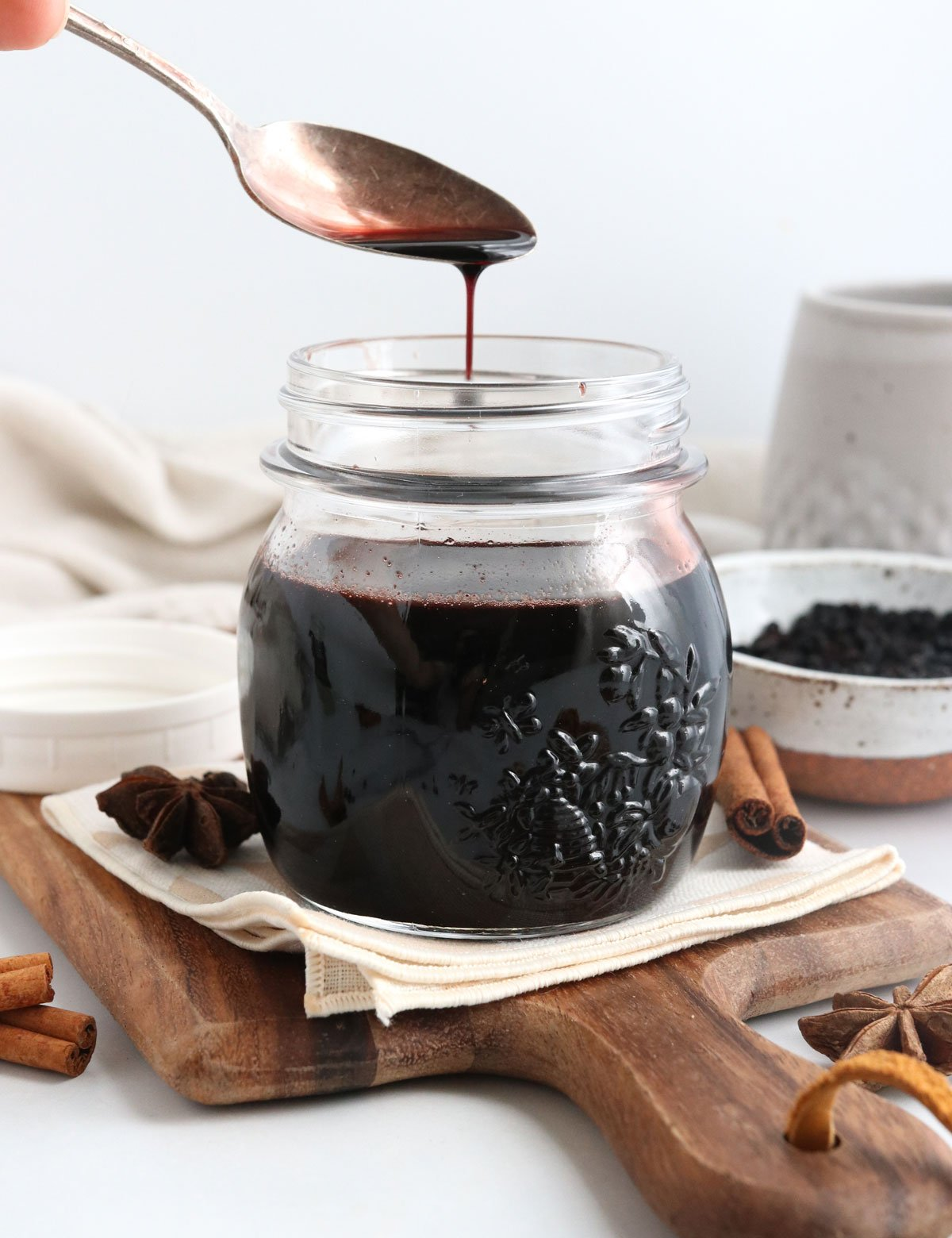 elderberry syrup pouring off of a spoon into jar