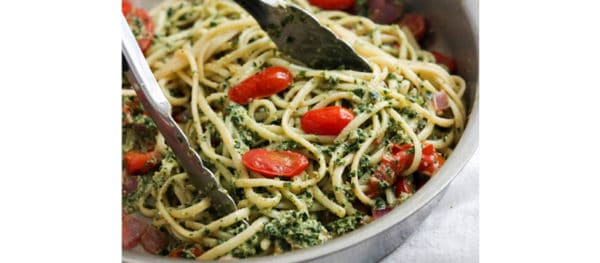 pasta and pesto tossed together in pan