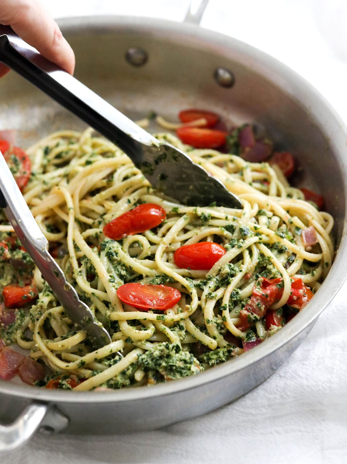 kale pesto tossed with noodles in pan