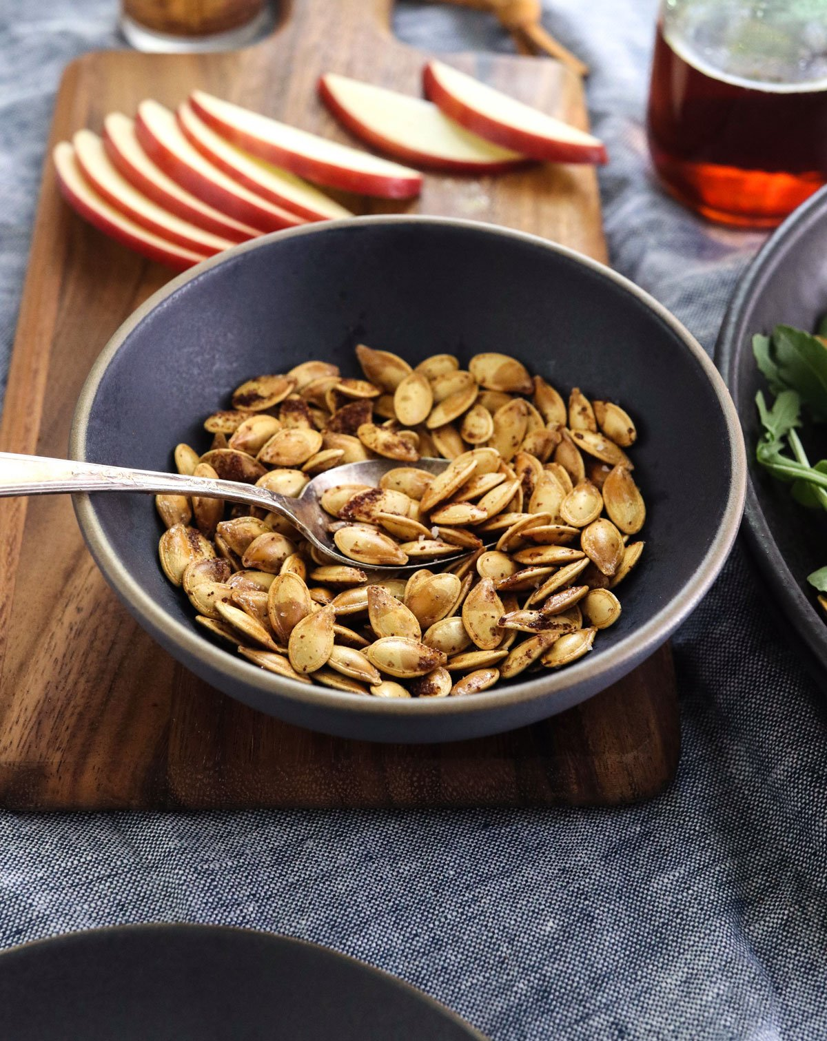 pumpkin seeds in dark bowl with salad ingredients