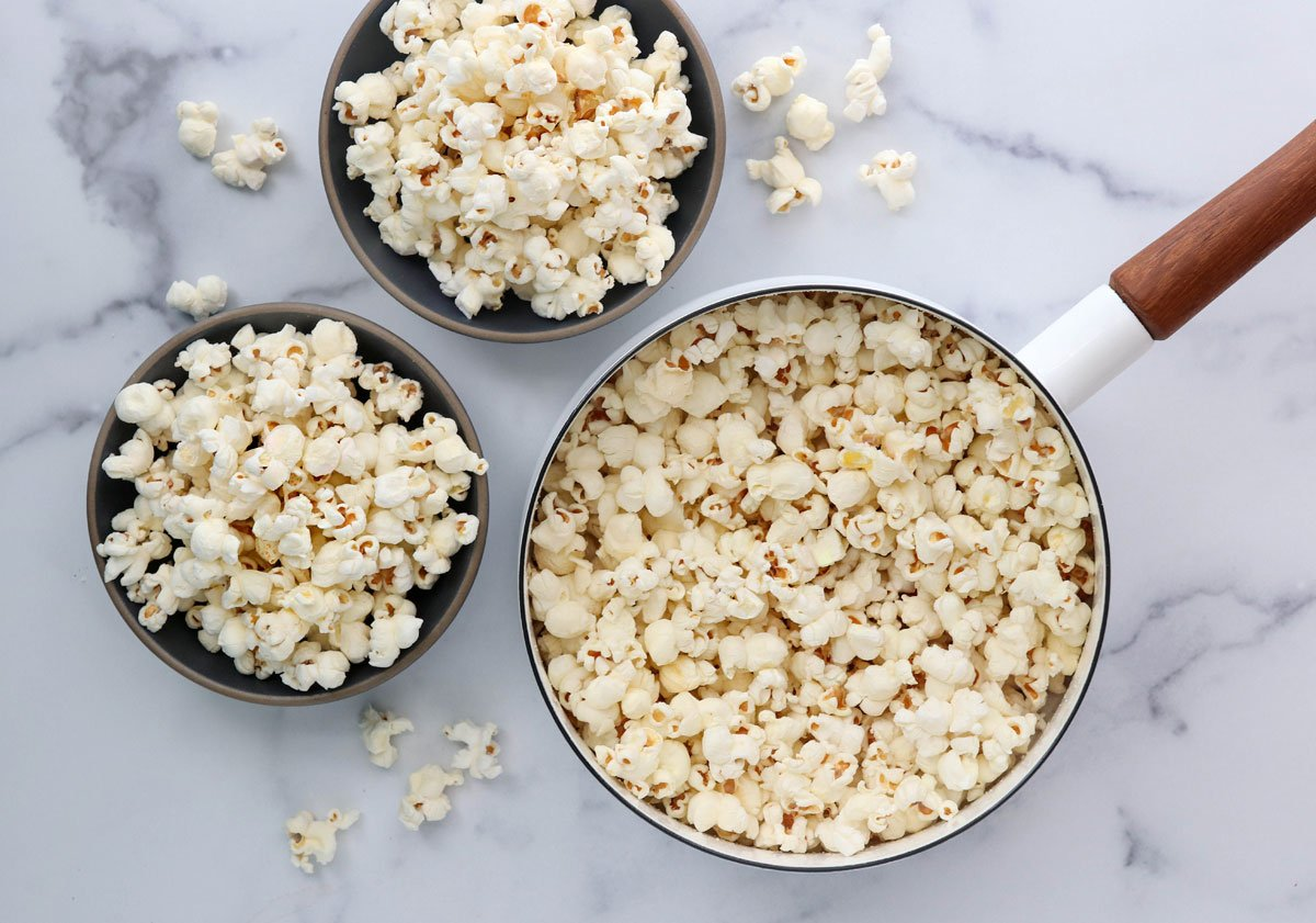 popcorn in pan and 2 bowls