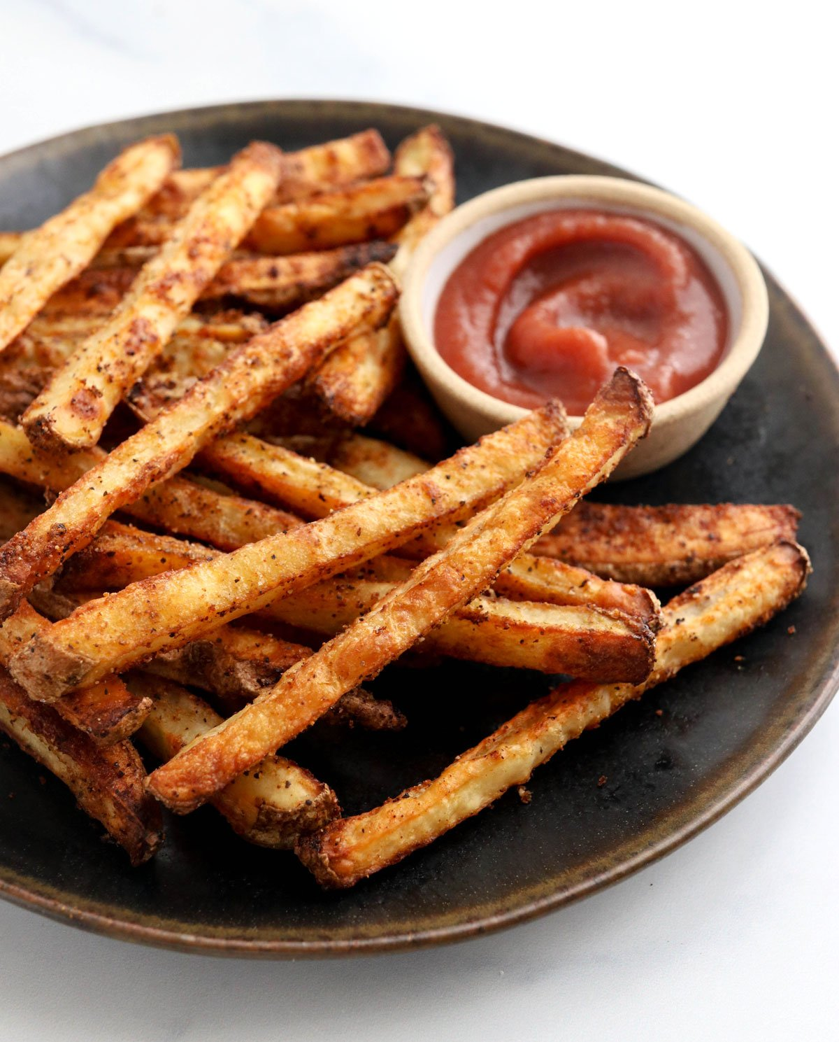 baked french fries on black plate with ketchup